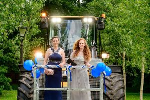Catherine Westgate (left) and Scarlett Weg arrive at the prom at Broyle Place via tractor.