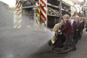 A Lewes Old Grammar Student learns how to use the firefighter's hose, photo by Peter Whyte