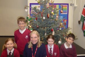 Holy Cross pupils and their teacher in front of the donated Christmas tree