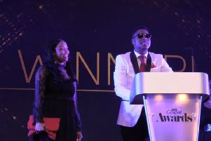 Chris Da Ambassada Grant on stage after receiving his reward, watched by his wife