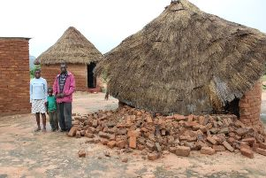 Nyasha with his cousins Shantel and Andrew standing in front of their house, which collapsed whilist he was in sleeping during Cyclone Idai in Zimbabwe.