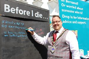Billy Blanchard-Cooper writing on the Before I die... board during Dying Matters Week