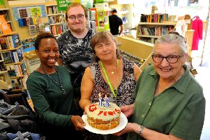 Manager Teresa Boyle and volunteers with the birthday cake at Oxfam bookshop, which now includes a range of donated clothes for sale as well