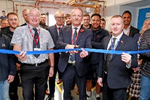 David Phillips, executive director for City & Guilds (centre) cuts the ribbon, with Steve Willis