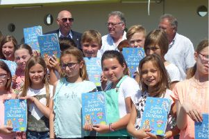 Rotarian Terry Herbert and mayor Gerard Delahaye with the children and their new Rotary dictionaries