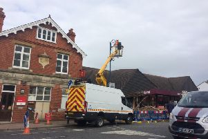 Fire and rescue workers remove the light from a lamppost next to Sainsbury's while clearing the area.