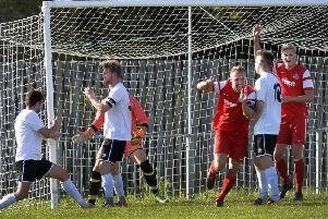 Tom Gilbert (centre, red) and Dean Bown celebrate against Eastbourne United. Picture by Jon Rigby.
