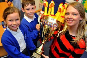 Emma Shaw presenter at Beano.com hands over the trophy to Macie Rowland and Samuel Kemp