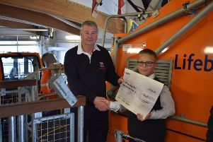 Logan Morris presenting his cheque to the RNLI