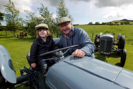 """Robert Berry, Farm Manager at the Ulster Folk Museum in Cultra, shows budding farmer Matthew Gardner from Holywood some of the fleet of Ferguson tractors that will be on display at the museum at this year�""""s Ferguson Heritage Tractor Day on Saturday, June 29."""