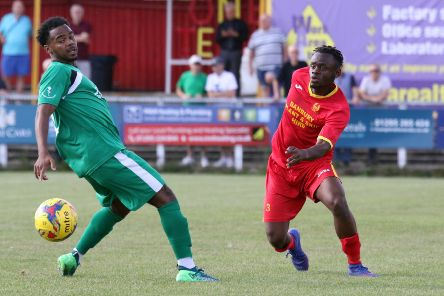 Banbury United's Gedeon Okito gets his pass away before Hitchin Town's Alexander Anderson can close him down. Photo: Steve Prouse