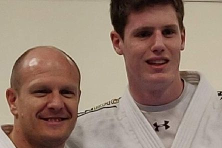 Sam Collins, right, is presented with his black-belt by coach Laurie Rush.