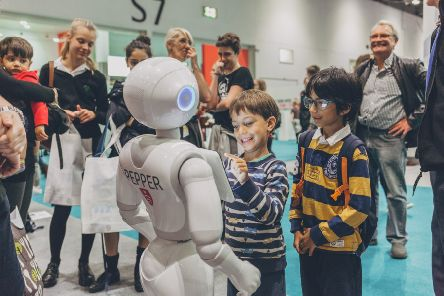 Children interact with a robot at the science fair