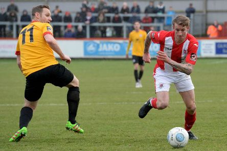 Brackley Town's Carl Baker goes past Bradford Park Avenue's Nicky Clee. Photo: Jake McNulty