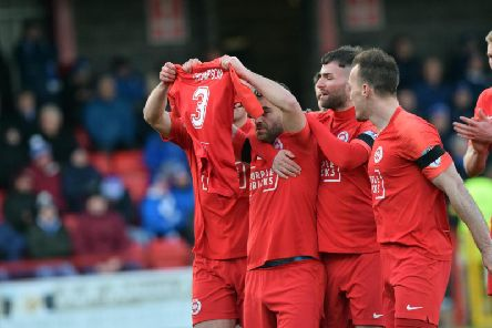 Davy McDaid celebrates his opener for Larne with a tribute for former player Jerry Thompson