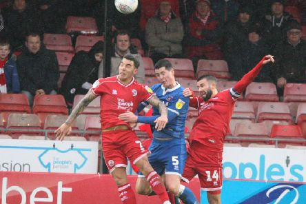 George Francomb (right) fights for a header against Carlisle. Photo: Derek Martin Photography
