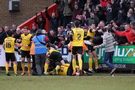 The Cobblers players and supporters celebrate Ricky Holmes' last-gasp winner at Stevenage in 2016