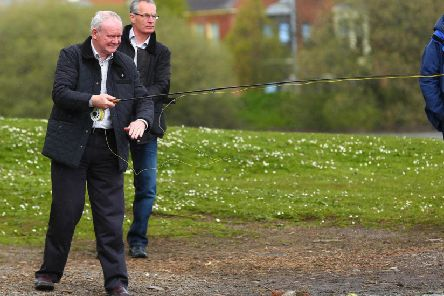 The late Martin McGuinness, pictured here casting a line out during canvassing with Gerry Kelly in Belfast in 2015. (Picture - Kevin Scott / Presseye News)
