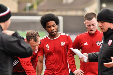 Derry City forward, Walter Figueira listens to instructions from Derry boss, Declan Devine during training at Brandywell