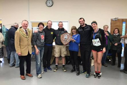 The Harriers collecting the winning team trophy at the Abbots Langley Tough Ten event.