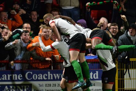 Glentoran players and supporters celebrate Patrick McClean's spectacular overhead kick to seal success over Larne. Pic by Pacemaker.