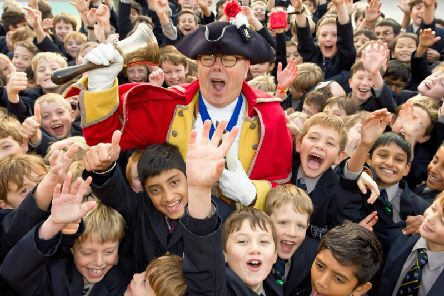 Warwick Town Crier, Michael Reddy, with pupils at Warwick School. Photo supplied.