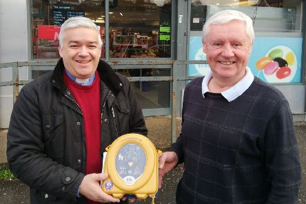 Rev. James Boyd, rector of St Columba's, presents a defibrillator to Ian Hall, owner of Mace Supermarket, Moss Road
