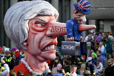 British Prime Minister Theresa May is depicted with a Pinocchio nose reading 'Brexit' piercing a representative of the British economy on a carnival float at the Rose Monday carnival street parade in Duesseldorf, western Germany, on March 4, 2019. Photo credit INA FASSBENDER/AFP/Getty Images