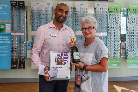 Lee Murphy collects her prize of champagne, a certificate and glasses voucher from Rishi Patel, store director at Specsavers' Rustington branch
