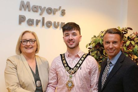 The new Mayor of Causeway Coast and Glens Borough Council, Cllr  Sean Bateson receives the chain of office from outgoing Mayor Councillor Brenda Chivers as Chief Executive David Jackson looks on.