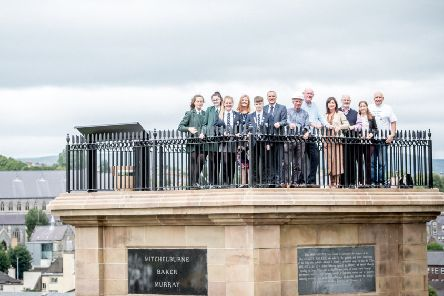 Pupils and principals of Lisneal College and St Cecilia's College with the project team at the top of the monument