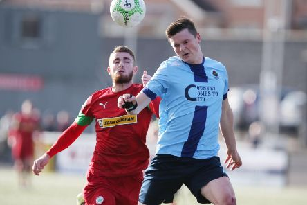 Cliftonville's Ruaidhri Donnelly puts Institute defender Shaun Leppard under pressure.