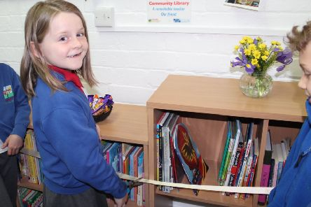 A pupil cuts the ribbon to open the library. The plaque in memory of Mrs Carne can be seen on the wall above.