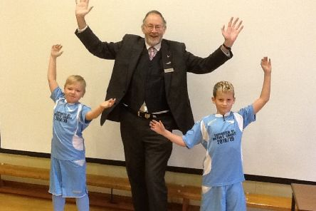Former Mayor, Steve Palmer, alongside two Sutton on Sea pupils in their football kits.