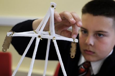 A pupil at Haven High Academy, in Boston, demonstrates the creation of a modern pylon in one of the school workshops. (Photo: John Robertson/National Grid).