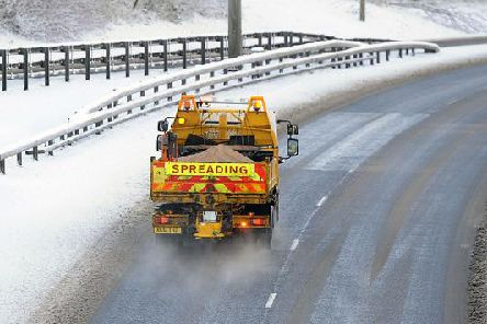 A gritter in action during snowy weather conditions.