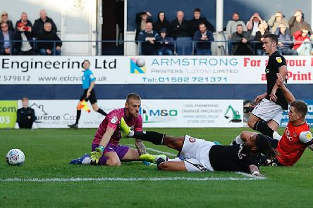 City defender Ashley Williams slides the ball past his own keeper Daniel Bentley for Luton's third on Saturday