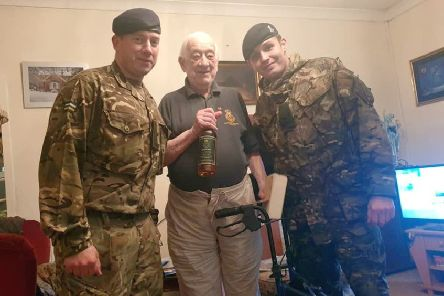 Stan perry receives his birthday dram from LCpl Campbell and LCpl Macdonald.