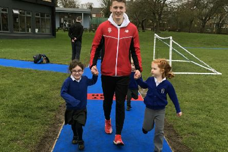 GB athlete Ben Higgins with pupils of Whissendine Primary School as he launched its new Daily Mile track EMN-190802-121739001
