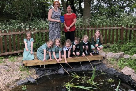 Teacher Frances Port (left) and pupils of St Mary's Primary School, Melton, at their wildlife pond with Melanie Swainston, of the Melton Building Society, which sponsored the clean-up work there EMN-190531-103654001