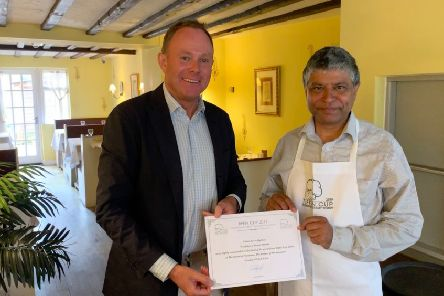Nick Herbert MP presenting owner Sanjay Jha with the certificate and Tiffin Cup apron