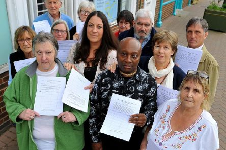 Councillor Stephen Hillier pictured with upset residents outside Boots Pharmacy in Haywards Heath. Photo by Steve Robards