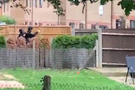 Armed police filmed in garden of home at the centre of armed siege