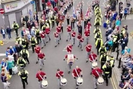 Clydevalley Flute Band flanked by PSNI officers during Saturday's parade. The Larne band shared the picture on its Facebook page.