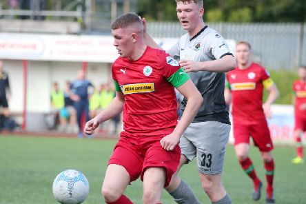 Cliftonville's Aaron Donnelly shields the ball from Institute's debut boy Aaron McGurk.