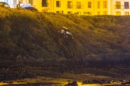 A car hangs onto the verge after going over the cliff in Portballintrae on Monday night - pic by McAuley Multimedia