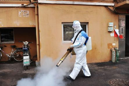 A worker wearing a protective suit sprays disinfectant in a neighborhood in Qingdao in eastern China's Shandong Province. (Photo: Chinatopix via AP)