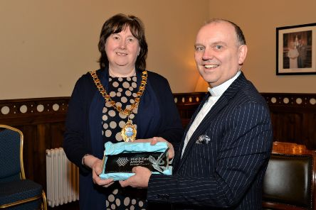 The Mayor of Mid and East Antrim Borough, Councillor Maureen Morrow, presents a gift to Rt Rev Dr William Henry, Moderator of the Presbyterian Church, during his visit to Larne Town Hall. INLT 05-002-PSB