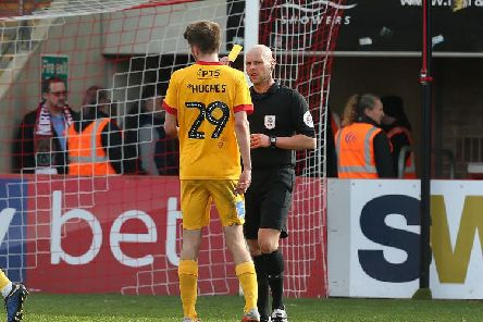 Teenager Ryan Hughes is shown yellow by referee Charles Breakspear after giving away a first-half penalty on his Cobblers debut at Whaddon Road. Pictures: Pete Norton