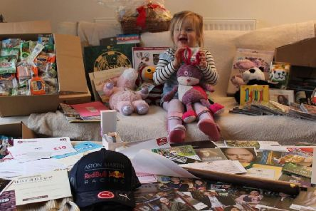 Three-year-old Imogen with some of the items in the upcoming charity auction